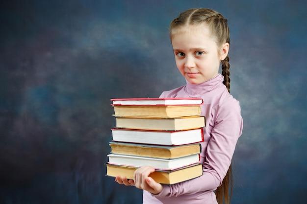 Веселая начальная школьница держит книжный букет