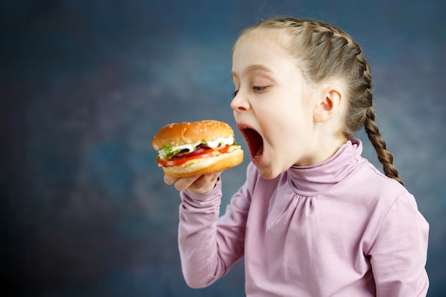 Американская калорийная жирная еда нездоровая пища, маленькая девочка любит есть гамбургеры фаст-фуд бургер нездоровый