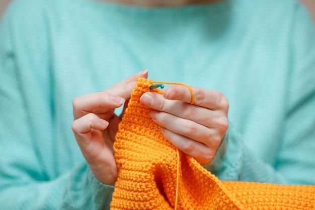 Девушка вяжет из трикотажной пряжи. вязание крючком толстые нити. домашний комфорт.