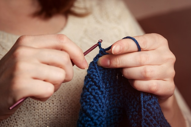 かぎ針編み。女性かぎ針編みダークブルーの糸。手のクローズアップ。
