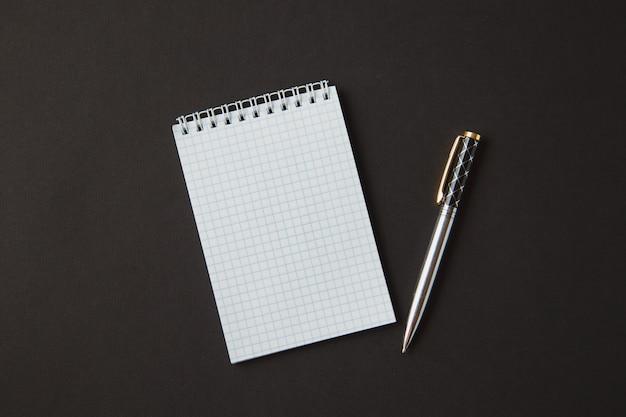 古い木製のテーブルの上にペンでノート