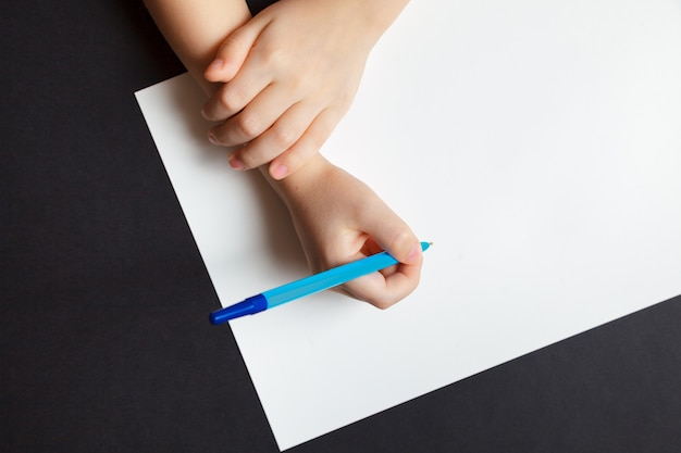 Руки ребенка на пустой белый лист бумаги