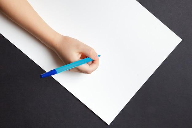 空の白い紙のシート上の子供の手