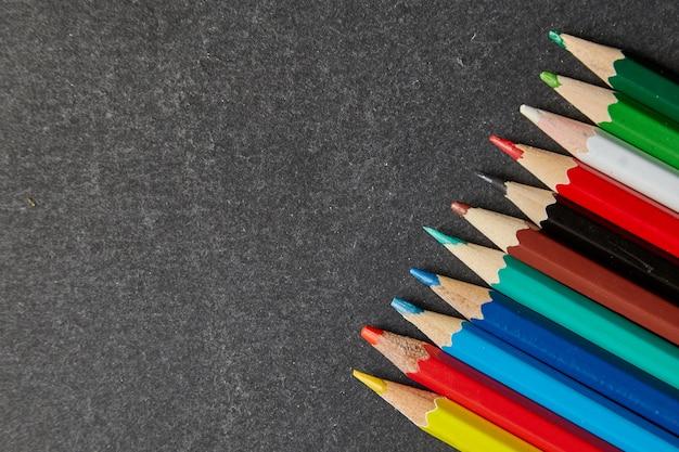 灰色の背景に色鉛筆。学校概念に戻る