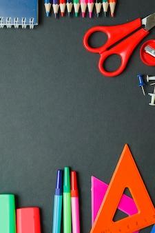 暗い背景に学校やオフィス用品。コピースペースのトップビュー