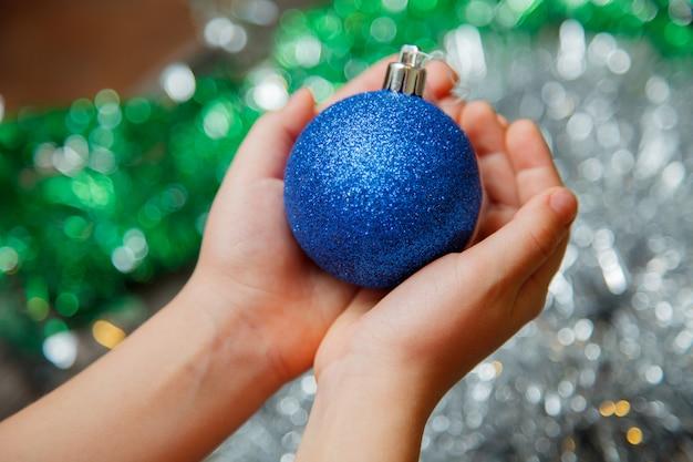 青いボール飾りを持っている手は、光沢のある背景に自宅のクリスマスツリーを飾ることをクローズアップ