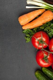 Предпосылка пустого черного цвета с свежими здоровыми овощами - зеленым луком, огурцом, томатами морковью и петрушкой. вид сверху.