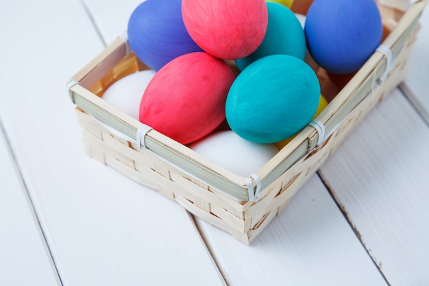 Пасха, праздники, традиции и концепция объекта - крупным планом цветных пасхальных яиц в корзине