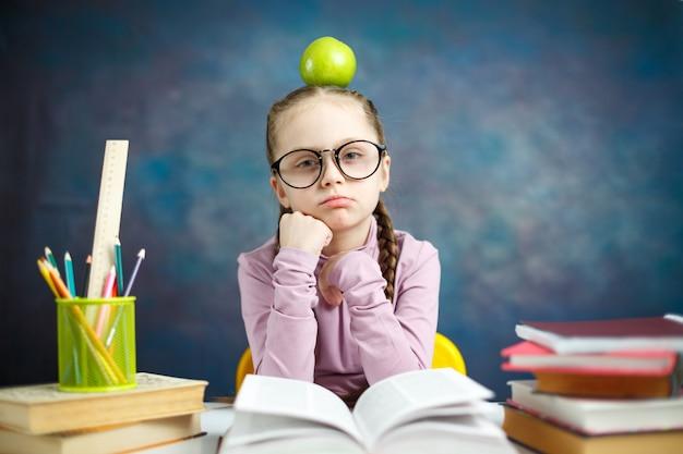 頭の上のリンゴと思いやりのある小学生の女の子