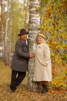 Активные пожилые люди на прогулке в осеннем лесу