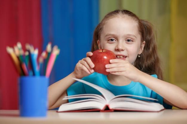 Портрет счастливой красивая девушка держит красное яблоко в классе