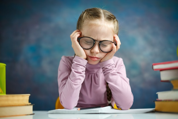 Маленькая начальная школьница читает книгу
