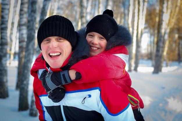 Молодой отец и сын в зимний пейзаж