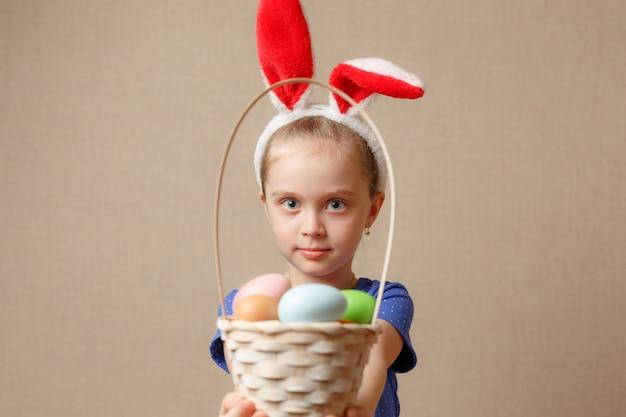Очаровательная маленькая девочка в ушах зайчика играет с пасхальными яйцами