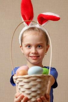 Маленькая девочка в ушах зайчика держит корзину с пасхальными яйцами