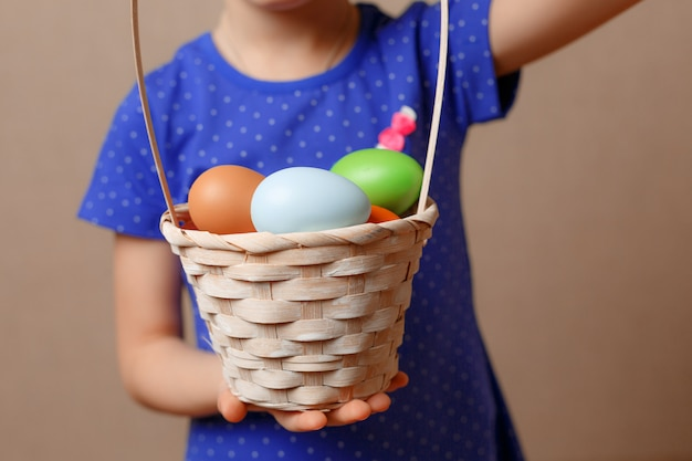 Девушка держит корзину с крашеными яйцами.