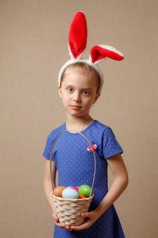 Уши зайчика милого маленького ребенка нося на день пасхи. девушка держит корзину с крашеными яйцами.