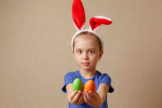 Милая маленькая девочка с ушами зайчика и пасхальными яйцами. выборочный фокус