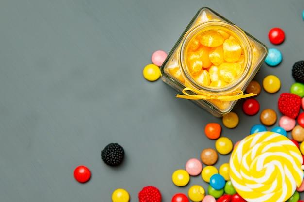 灰色の木製の背景にさまざまな形や色のお菓子。ソフトフォーカス