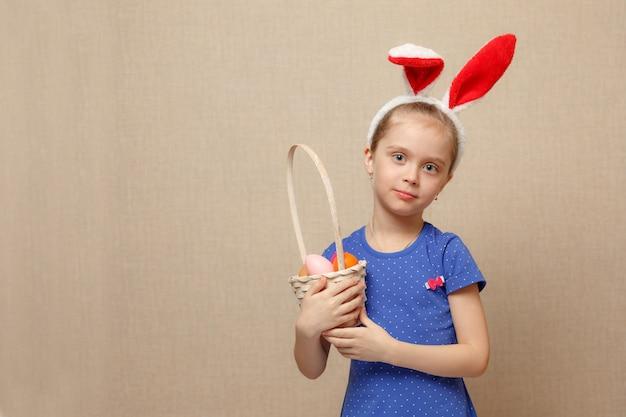 Маленькая девочка с корзиной пасхальных яиц