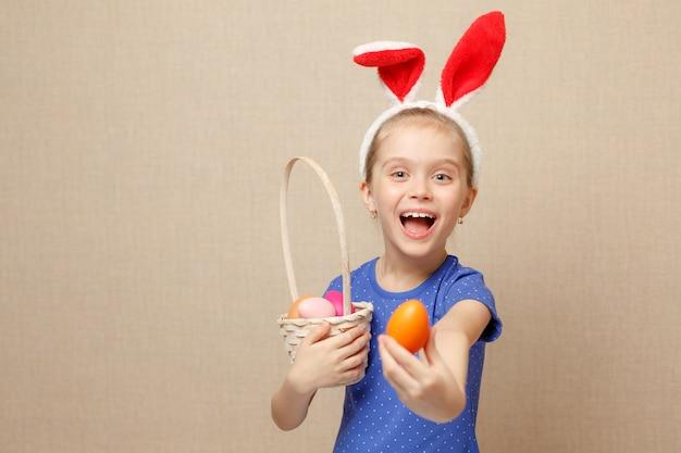 Счастливый ребенок девочка с ушками зайчика и пасхальных яиц