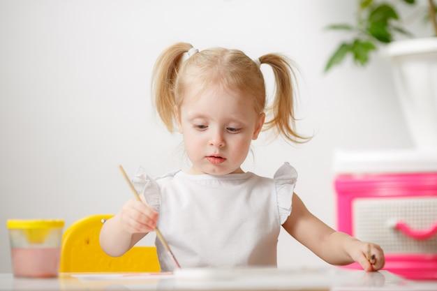 彼女の部屋で家にいる間、少女は水彩画を描きます。子供は創造性に従事しています。リトルアーティスト。