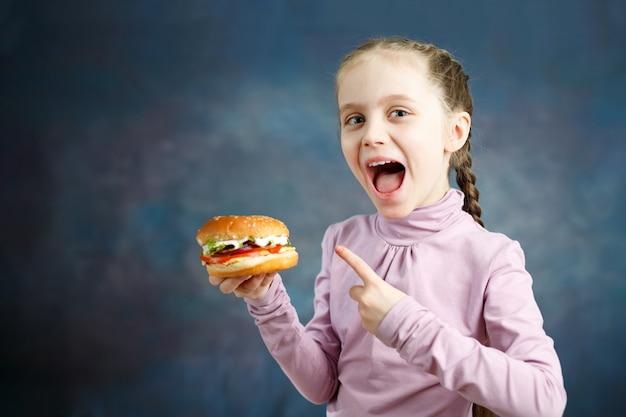 美しいかわいい白人の女の子は彼女の手でハンバーガーを示しています