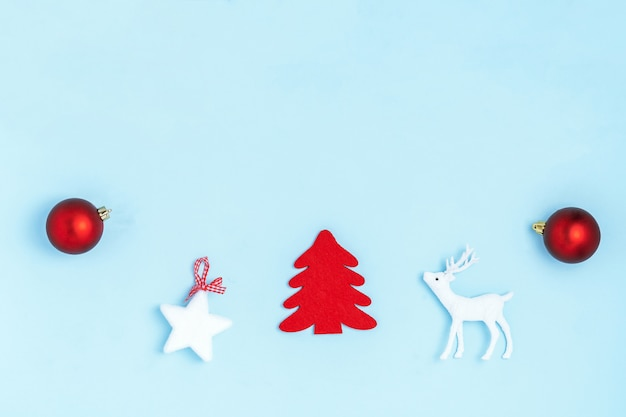 新年とクリスマスの組成。赤いボール、白い星、クリスマスツリー、鹿、パステルブルーの紙の背景に輝くフレーム。トップビュー、フラットレイアウト、コピースペース