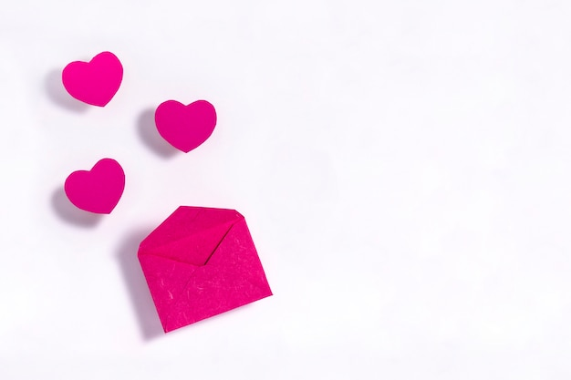 白い表面上の封筒とピンクの心