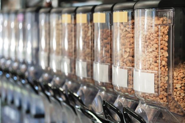 Диспенсеры с гайками в нулевом магазине отходов. новая тенденция альтернативной покупки. ноль отходов, экологичная концепция. концепция устойчивого образа жизни.