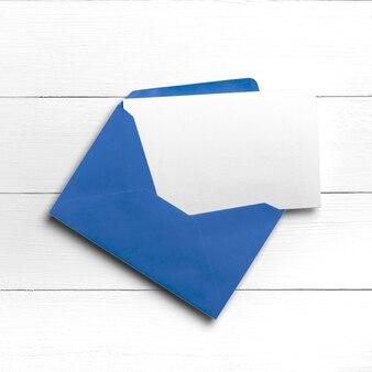 はがきまたは白い木製のテーブルのグリーティングカードと青い封筒