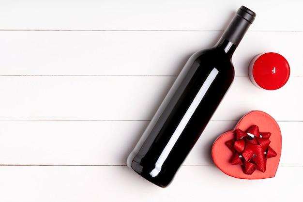 心、キャンドル、白い木製の表面にワインのボトル。バレンタインデーのコンセプト。平置き