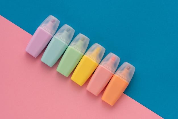蛍光ペンは、色付きの青ピンクの背景に設定します。マーカーの異なる色のコレクション。フラット横たわっていた、トップビュー。学校に戻って、教育の概念。