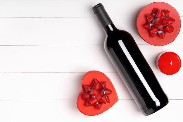 心、キャンドル、白い木製の表面にワインのボトル。バレンタインデーのコンセプト。フラットレイアウト、トップビュー、上から、コピースペース