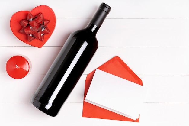 心、ろうそく、ワインの瓶、白い木製の表面の手紙と封筒。バレンタインデーのコンセプト。フラットレイアウト、トップビュー、上から、コピースペース