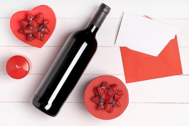 心、ろうそく、ワインの瓶、白い木製の表面の手紙と封筒。バレンタインデーのコンセプト。フラットレイアウト、トップビュー、上から