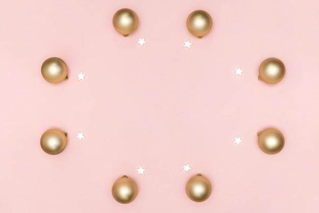 新年とクリスマスの組成。ゴールデンボールからフレーム、パステルピンクの紙の背景に白い星。トップビュー、フラットレイアウト、コピースペース