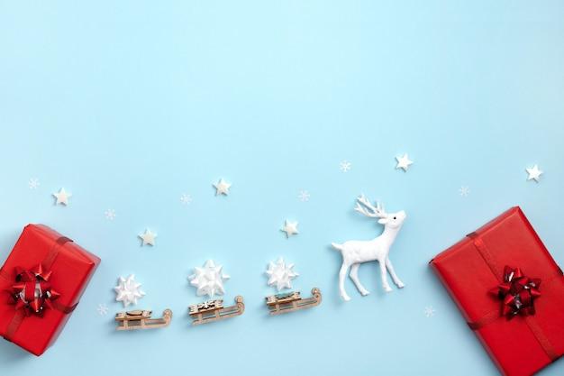 新年、クリスマスフレーム、グリーティングカード。白い星、サンタのそりと鹿、パステルブルーの紙の背景にギフトボックス。トップビュー、フラットレイアウト、コピースペース。