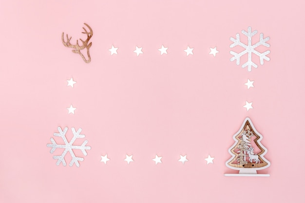 クリスマスの組成物。白い星、雪、クリスマスツリー、パステルピンクの紙の背景に鹿のシンボルからフレーム。トップビュー、フラットレイアウト、コピースペース。