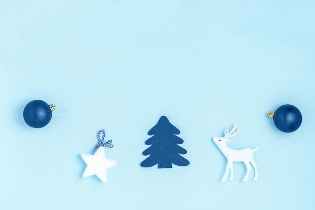新年とクリスマスの組成。青いボール、白い星、クリスマスツリー、鹿、パステルブルーの紙の背景に輝くフレーム。トップビュー、フラットレイアウト、コピースペース