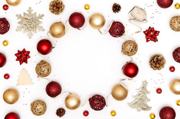 新年とクリスマスのフレーム。赤と金色のクリスマスの装飾-ボール、星、松ぼっくり、白い背景の上の装飾的なリボン。新年、クリスマスのコンセプト。トップビュー、フラットレイアウト、コピースペース