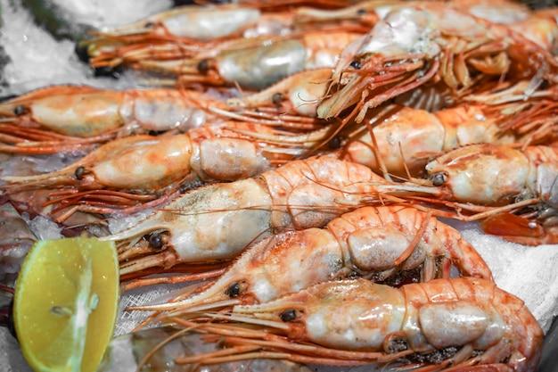 魚市場で氷の上で新鮮なエビ