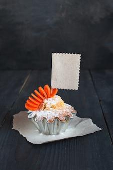 木製のテーブルに空のタグが付いたカップケーキ