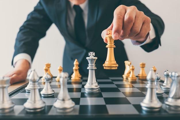 チェスをしているビジネスマンのリーダーシップとクラッシュについての思考戦略計画は反対のチームを倒し、開発は企業の成功のために分析します