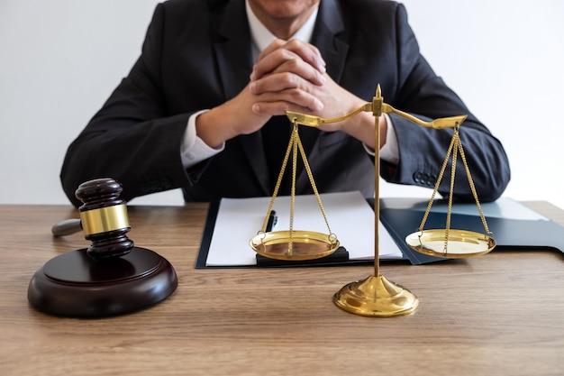 Правовое право, совет и концепция правосудия, юрист-консультант или нотариус, работающий над документами и отчетом о важном деле и деревянным молотком, латунная шкала на столе в зале суда