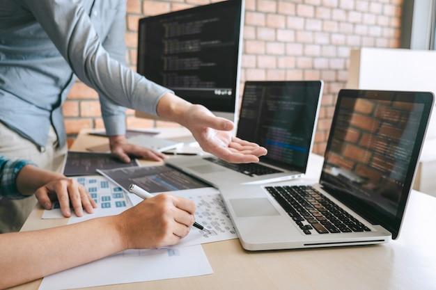 Профессиональная встреча разработчиков и программистов на мозговом штурме и программировании на веб-сайте, где используется технология аутсорсинга и кодирования программного обеспечения, написание кодов и базы данных
