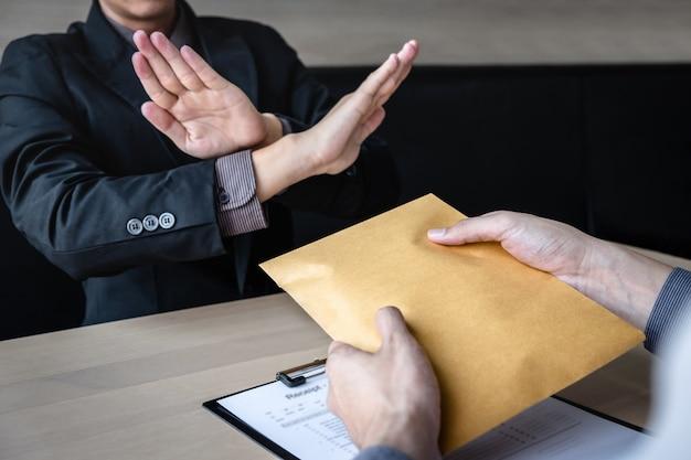 贈収賄および汚職防止の概念、ビジネスマンが拒否し、投資取引の契約契約を受け入れるためにビジネス人々からの包み込みのお金の紙幣を受け取らない