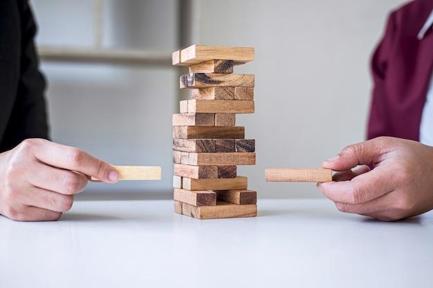 ビジネスにおける代替リスクと戦略、ビジネスチームの協力的ギャンブルの協力タワーへの木製ブロックの階層化の作成