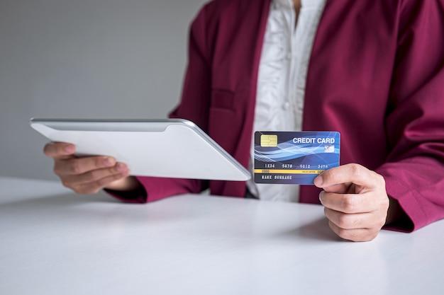 デジタルタブレット、クレジットカードを保持し、オンラインショッピングと支払いのためのタイピングを保持している若い女性消費者は、インターネット、オンライン支払い、ネットワークで購入し、製品技術を購入