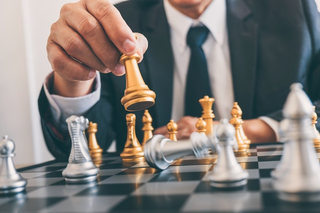 Лидерство бизнесмена, играющее в шахматы и продуманный стратегический план о крушении свергает противоположную команду и анализирует развитие на предмет успешности корпоративного